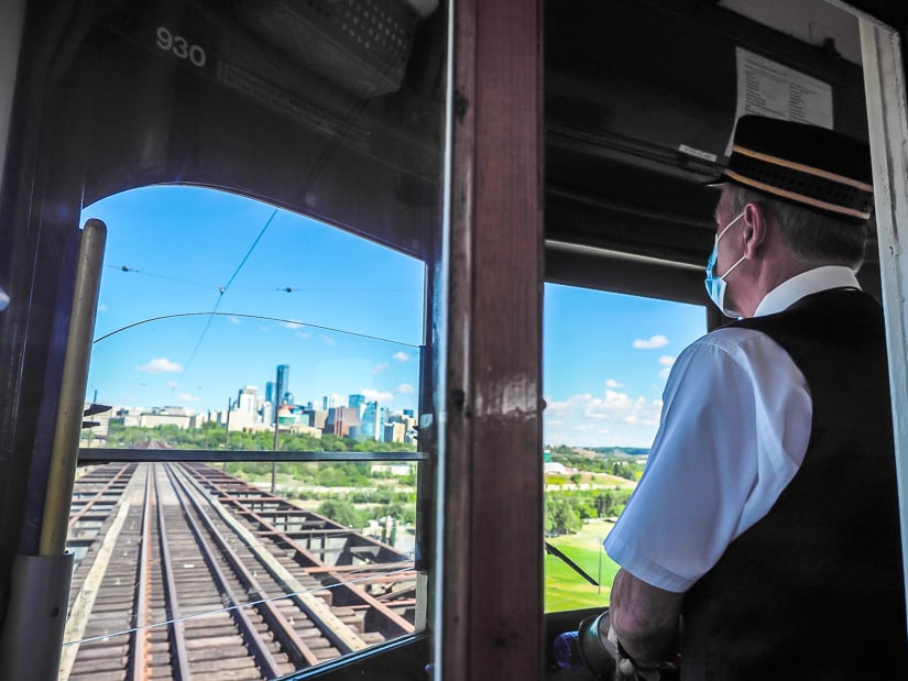 A streetcar driver driving across the highest streetcar bridge in the world in Edmonton.
